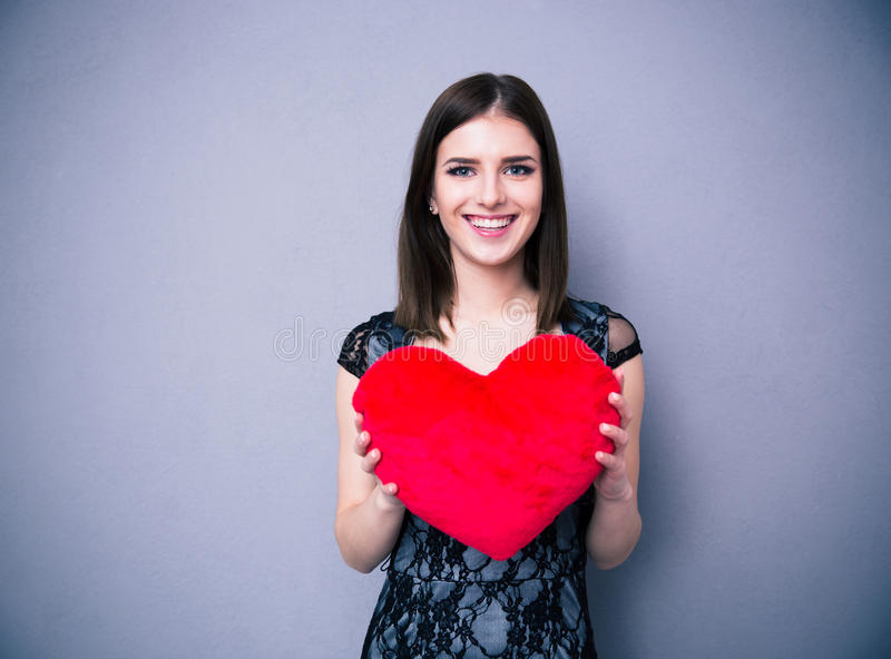 Smiling beautiful woman in dress holding red heart. Over gray background and looking at camera royalty free stock image
