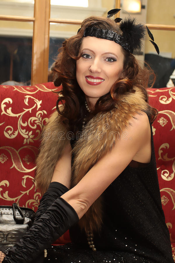 Smiling beautiful woman in evening gown and furs. In the luxurious interior royalty free stock images