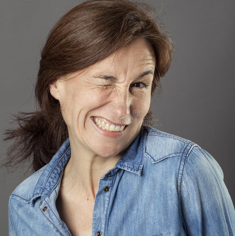 Smiling beautiful woman having fun in winking for wellbeing. Smiling beautiful middle aged woman having fun in winking for wellbeing and happy flirting, wearing royalty free stock photo