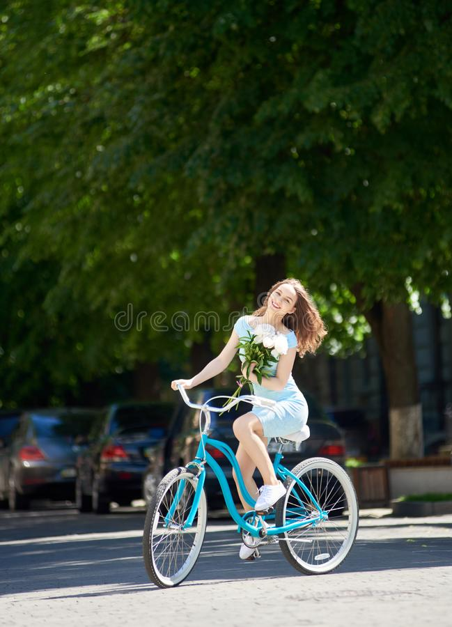 Smiling beautiful woman holding peonies and riding blue bicycle down empty paved street with green trees around. royalty free stock image