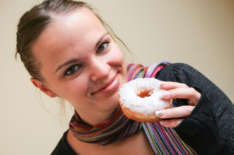 Smiling beautiful woman is holding a donut in white glaze stock image