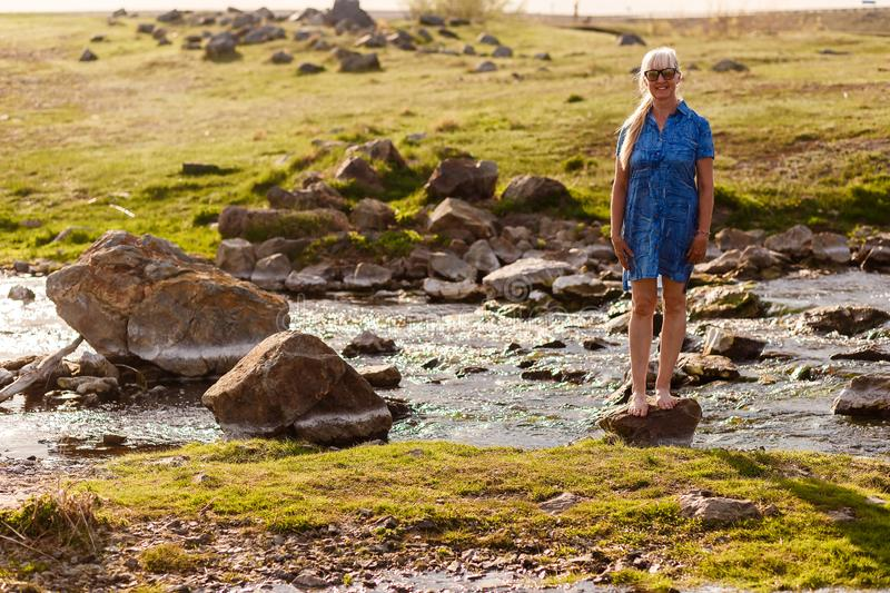 Smiling beautiful woman of retirement age in a blue dress standing on a stone near the river at sunset stock photos