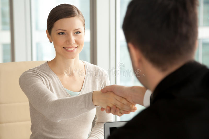 Smiling beautiful woman shaking male hand, arriving at job inter stock images