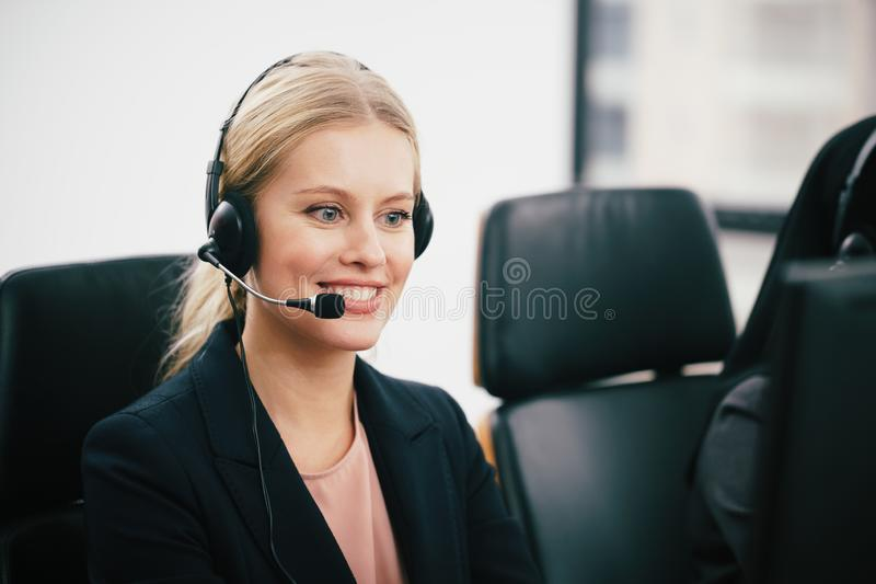 A smiling  beautiful woman sitting in a customer service department office with headset working in call center royalty free stock photo