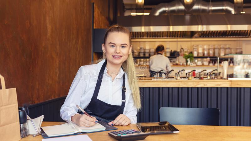 Smiling beautiful woman sitting in small family restaurant calculating finance bills and profit royalty free stock photography