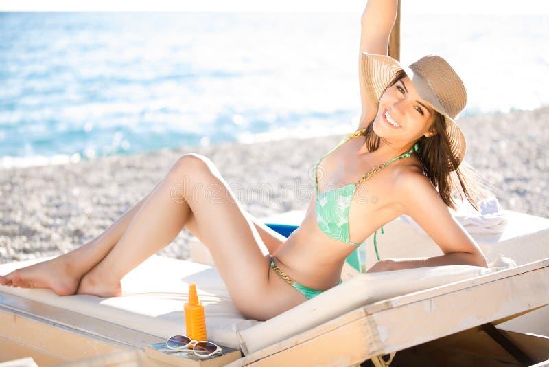 Smiling beautiful woman sunbathing in a bikini on a beach at tropical travel resort, enjoying summer holidays. Young woman lying. On sun lounger near the sea royalty free stock photos