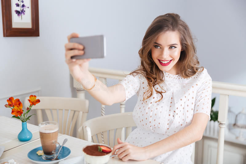 Smiling beautiful woman taking selfie with smartphone sitting in cafe. Smiling beautiful young woman in white dress taking selfie with smartphone sitting in cafe stock image