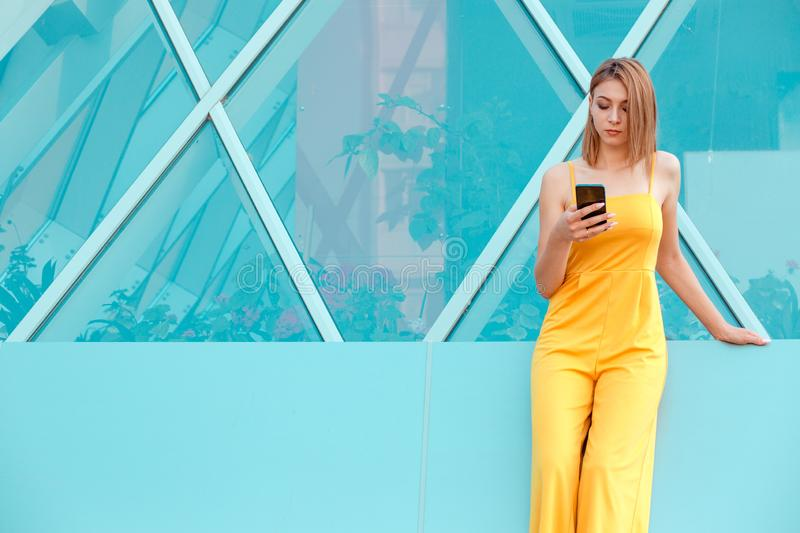 Smiling beautiful woman texting on her smart phone stock photos