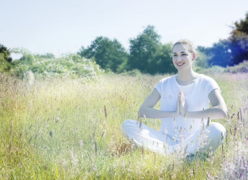 Smiling beautiful yoga girl relaxing on grass for romantic happiness. Smiling beautiful yoga girl seated on grass, relaxing for happiness, romantic serenity and stock images