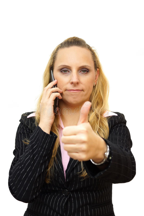 a smiling beautiful young business woman with a mobile phone posing with the thumbs up sign stock photo