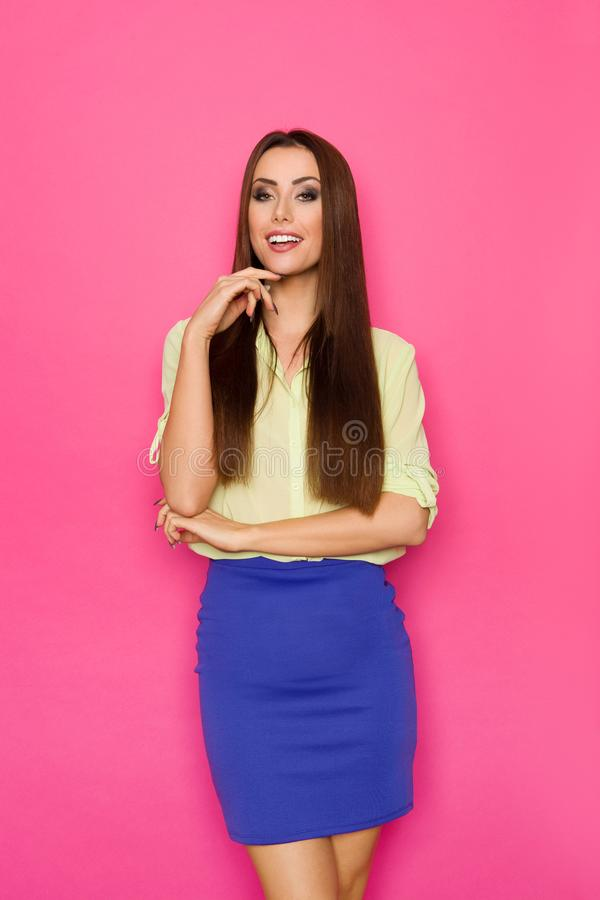 Smiling Beautiful Young Woman In Blue Mini Skirt And Green Shirt. Beautiful young woman in blue mini skirt and green shirt is posing with hand on chin, looking stock images