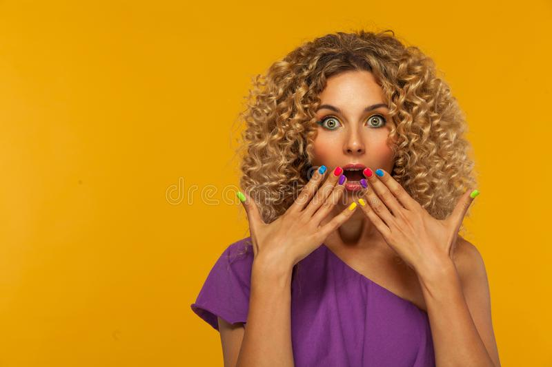 Smiling beautiful young woman with colorful manicure. Girl with afro hairstyle and braces. Yellow background. stock image