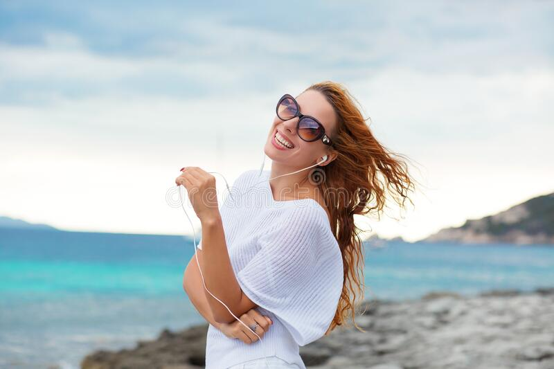Smiling beautiful young woman enjoying her summer vacation on the beach. Beautiful female model in sunglasses having fun on the. Sea shore background royalty free stock photos