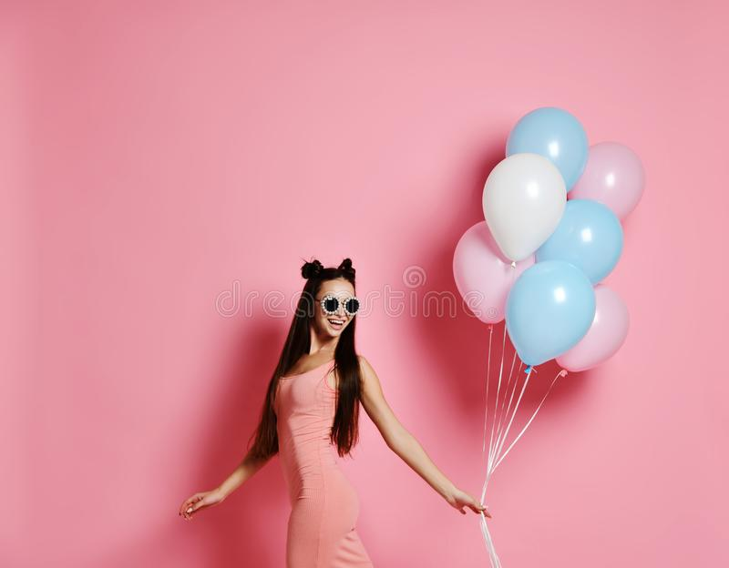 Happy and woman posing with pink and blue balloons on pink background, studio shot. Smiling beautiful young woman posing with pink and blue balloons on pink royalty free stock photo