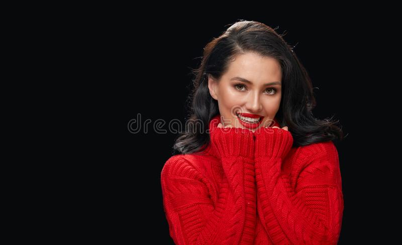 Woman in red sweater on black background stock images