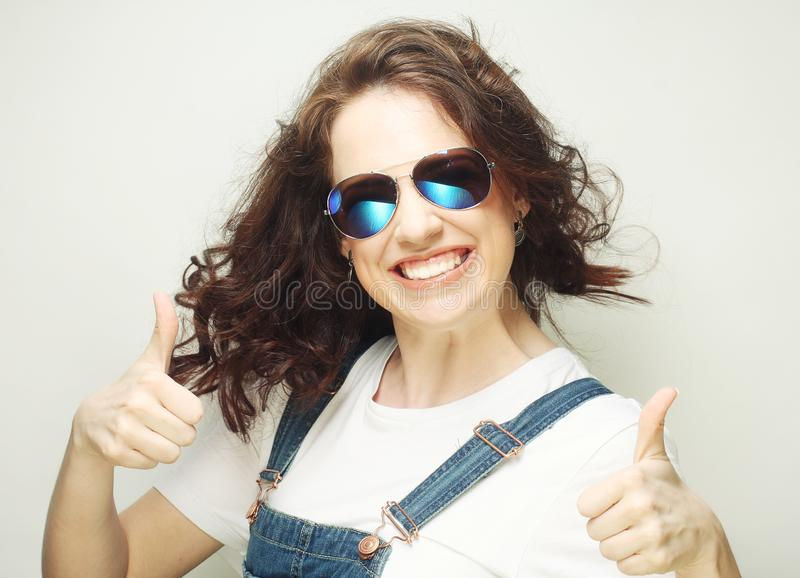 Smiling beautiful young woman showing thumbs up gesture. Happy smiling beautiful young woman showing thumbs up gesture royalty free stock images