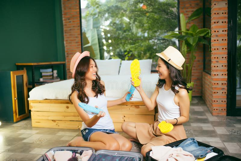 Smiling beauty sisters preparing luggage in living room and looking at schedule list checking all baggage already prepared.  royalty free stock image