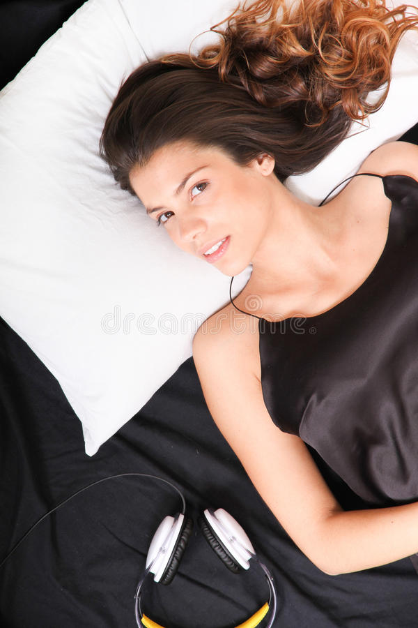 Smiling in bed with headsets. A young girl laying in bed, smiling with headsets royalty free stock photo