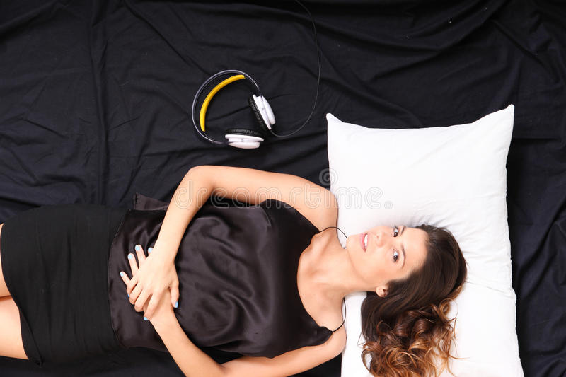 Smiling in bed with headsets. A young girl laying in bed, smiling with headsets royalty free stock images