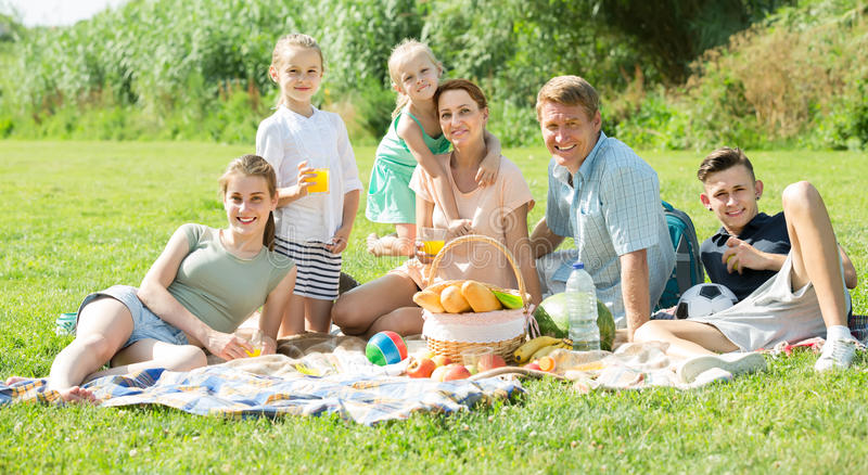 Smiling big family having picnic on green lawn in park stock image