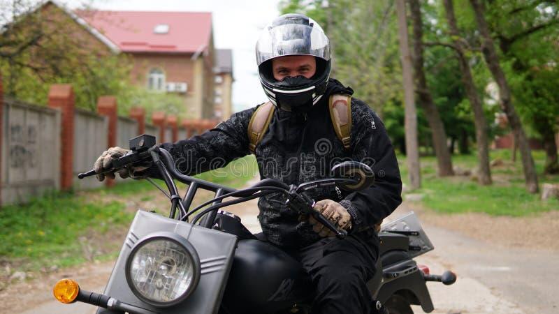 Smiling Biker man in a helmet sitting on his motorcycle. Smiling Biker man in a helmet sitting on his black motorcycle royalty free stock photo