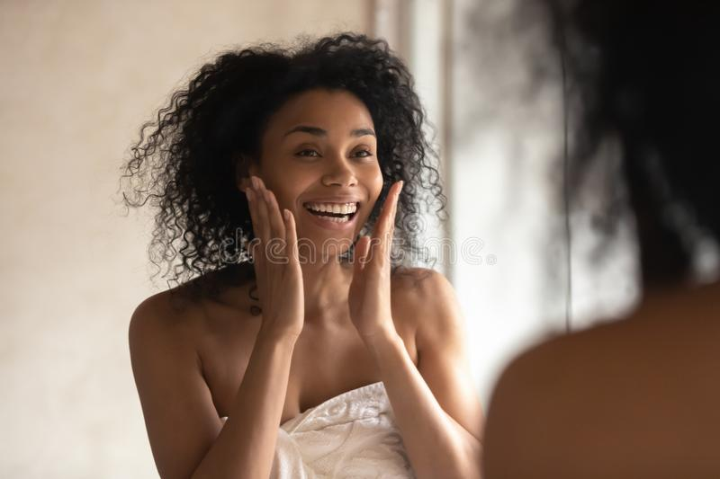 Smiling biracial woman look in mirror do facial procedures royalty free stock photography