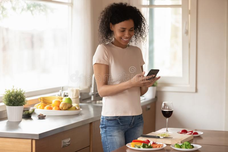 Smiling biracial woman texting on cell preparing food. Happy african American millennial woman chop slice vegetables drink wine cooking in kitchen using royalty free stock images