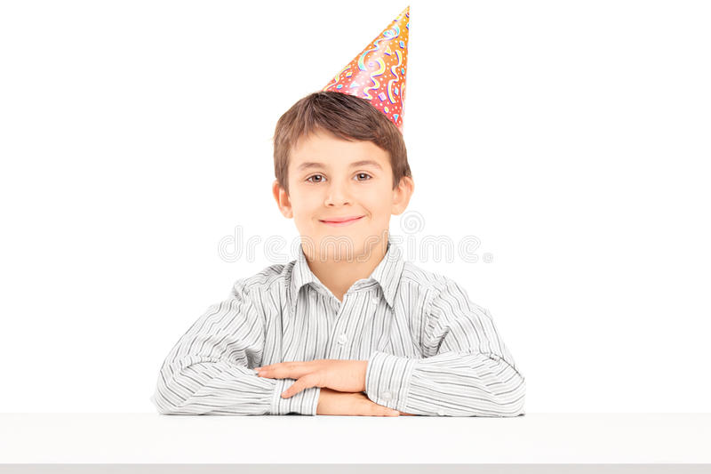 A smiling birthday boy with a party hat posing on a table. On white background stock photography