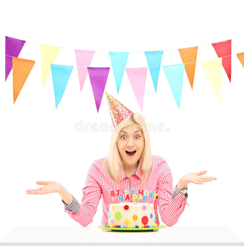 Smiling birthday female wearing party hat and gesturing. Isolated against white background royalty free stock image