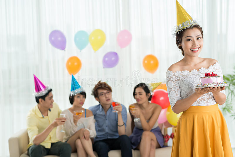 Smiling birthday girl. Portrait of smiling Vietnamese birthday girl holding a cake and her friends celebrating in background royalty free stock image