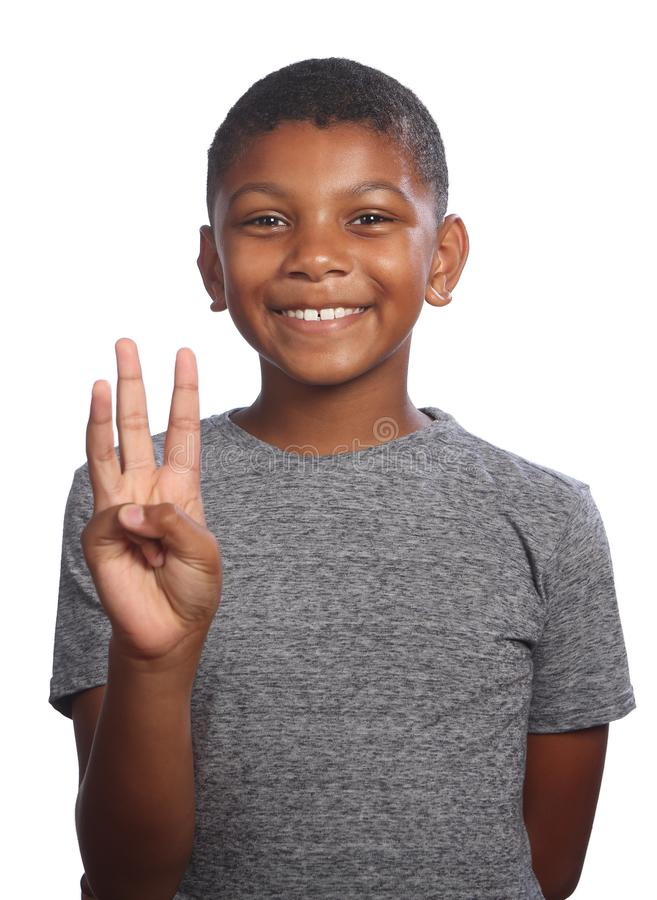 Smiling black boy showing number three on fingers stock image
