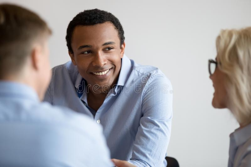 Smiling black businessman talk with colleagues at office meeting stock photos