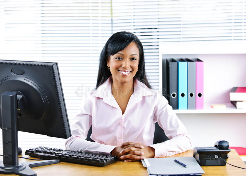 Smiling black businesswoman at desk. Portrait of smiling young black business woman at desk in office royalty free stock images