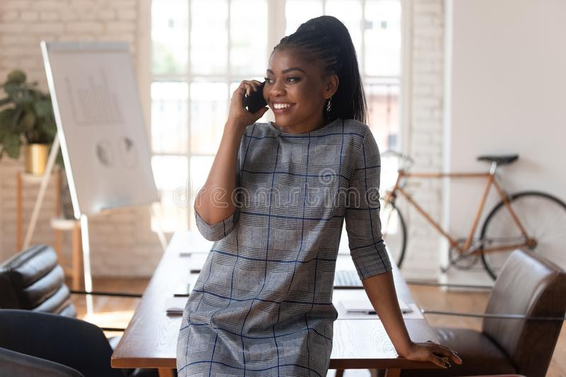 Smiling black businesswoman talking on phone making call in office royalty free stock photos