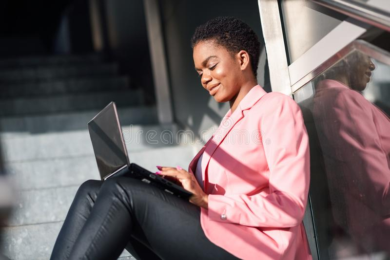 Smiling black businesswoman sitting on urban steps working with a laptop computer stock photography