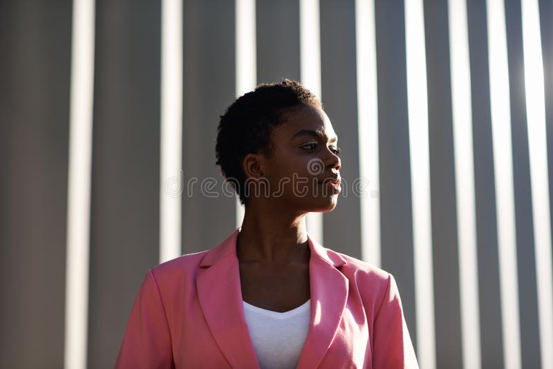 Smiling black businesswoman standing near business office building royalty free stock image