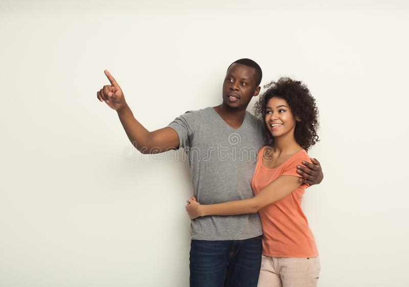 Smiling black couple embracing at white studio royalty free stock photo