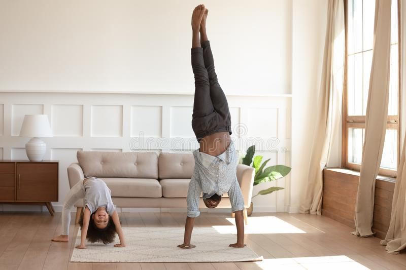 Smiling black family doing morning exercises together at home. stock image