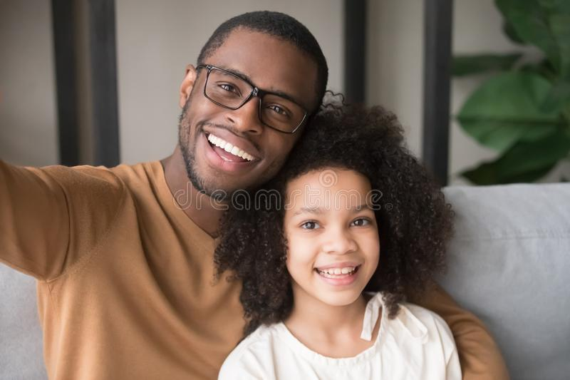 Smiling black father and child taking selfie looking at camera. Smiling black father and child daughter taking selfie together looking at camera, head shot royalty free stock photography