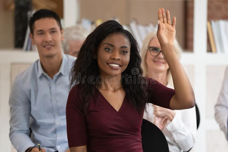 Smiling black female raise hand answering at seminar. Smiling african American female leader raise hand answer question at team training in office, happy stock photos