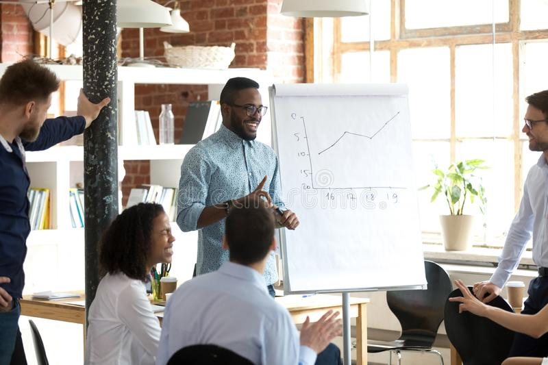 Smiling black leader or coach giving presentation at business meeting stock photos