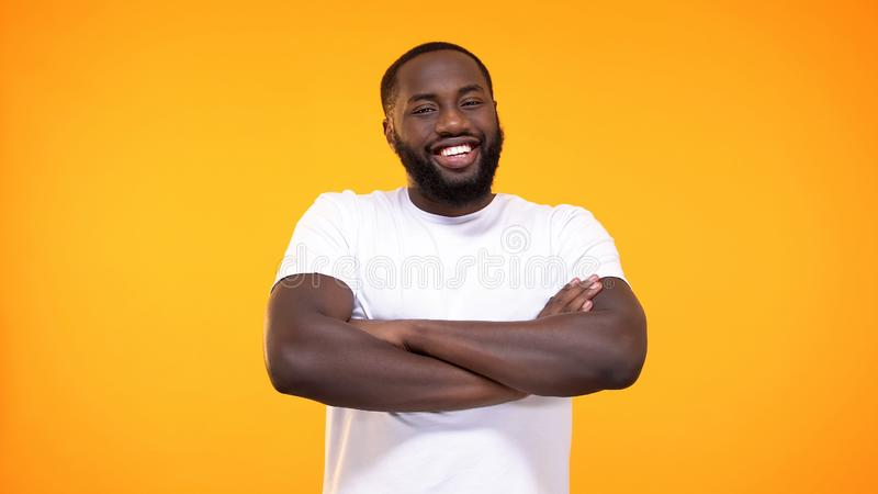 Smiling black male folded arms looking camera bright background, positive mood royalty free stock photography