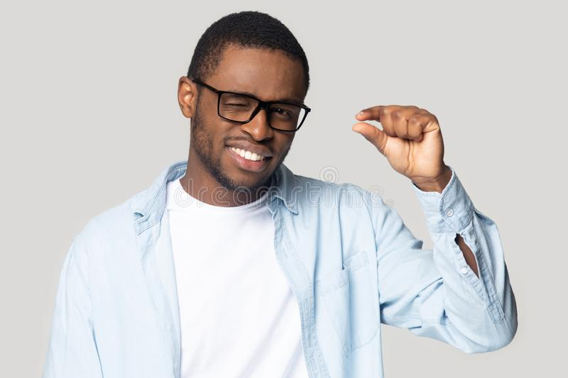 Smiling black male use hand show little measurement gesture stock images
