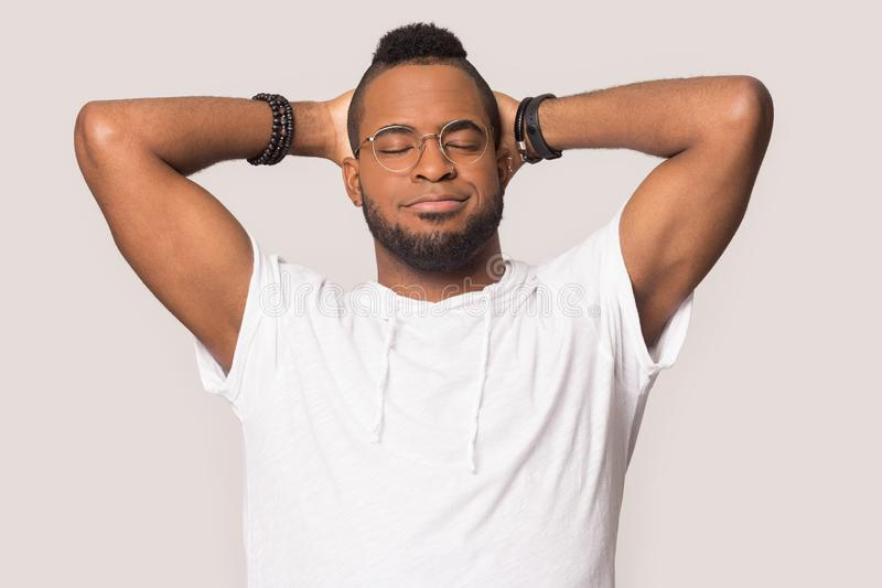 Smiling black man in glasses make selfie in studio. Smiling african American millennial male in glasses isolated on grey studio background make self-portrait stock image