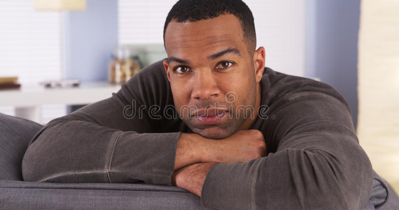 Smiling black man resting on couch royalty free stock photos