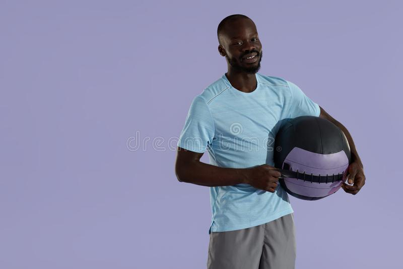 Smiling black man in sports wear with med ball studio portrait stock photography