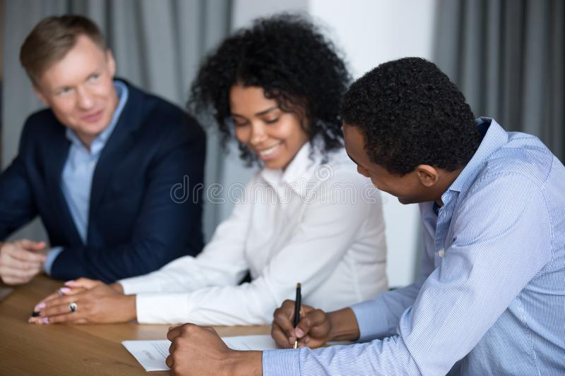 Diverse business partners close deal signing agreement at meeting. Smiling black men negotiate with diverse business partners sign cooperation deal at briefing royalty free stock image