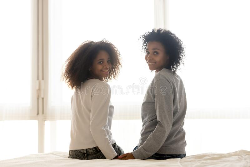 Smiling black mom and daughter sit on bed posing. Smiling African American mom and daughter sit on bed holding hands looking at camera, happy black mother and stock images