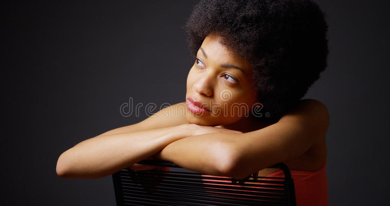 Smiling black woman sitting with arms over back of chair stock images