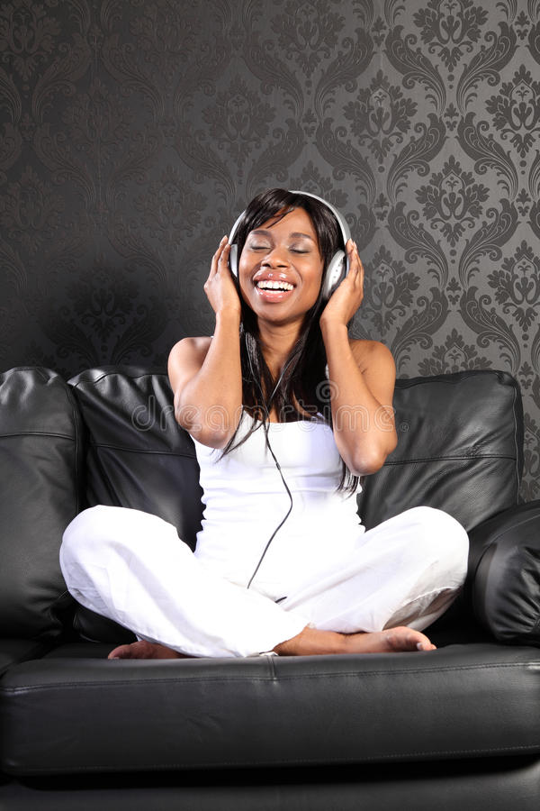 Smiling black woman on sofa listening to music. Beautiful smiling young african american woman sitting on black leather sofa at home, headphones on listening to royalty free stock photo